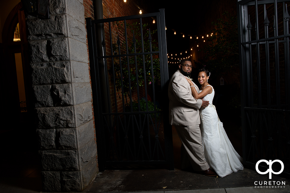 Bride and groom by an iron gate after their wedding at the Bleckley Inn in Anderson,SC.