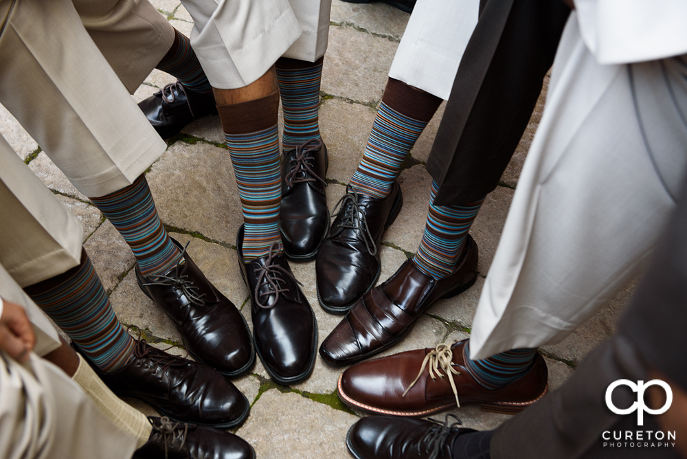 The groomsmen all showing off their matching socks.