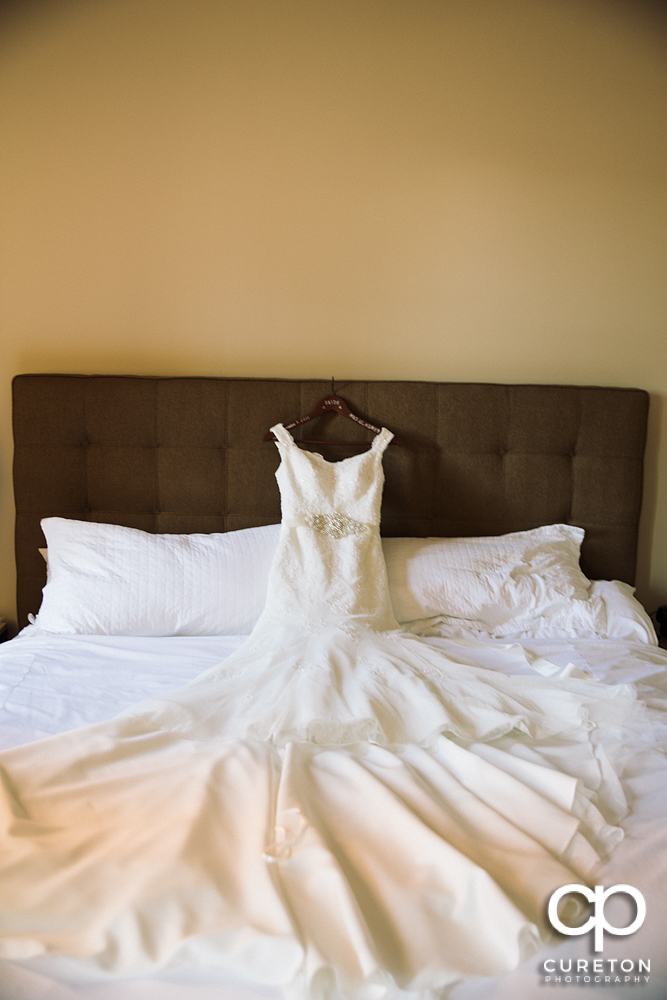 The bride's dress laying on the bed.