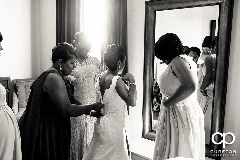 Bride putting on her dress with her mom and grandmother.