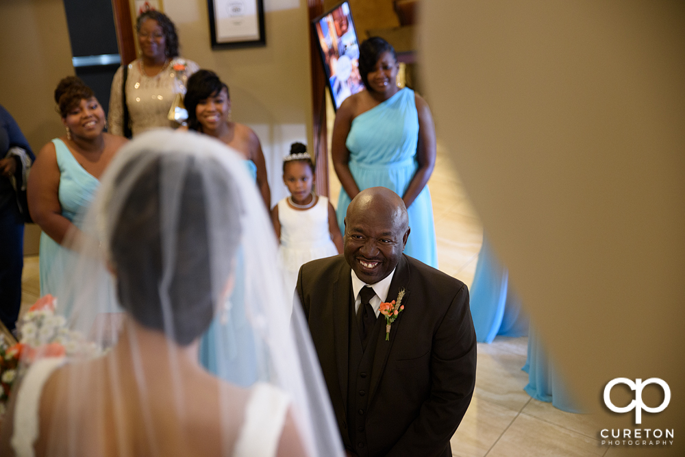 Bride's father smiling at her during the first look.