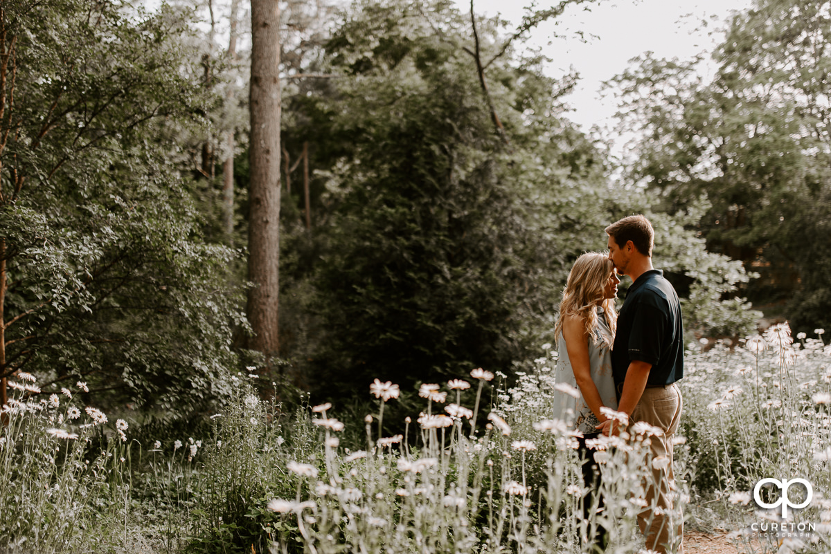 Future groom kissing his bride on the forehead in a field of wildflowers during their Botanical Gardens engagement session in Clemson,SC.