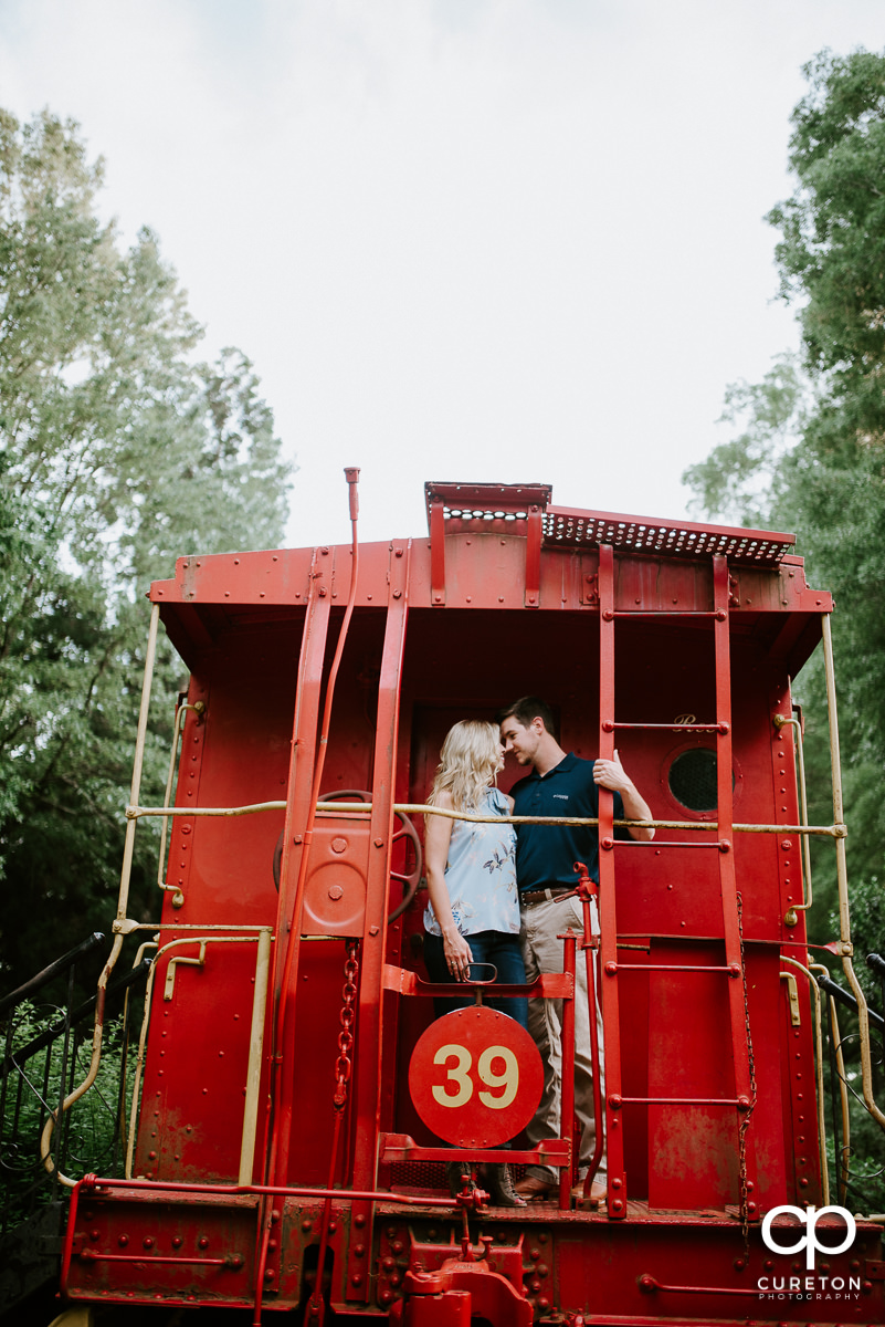 Bride and groom standing on a red train car during their Clemson Botanical Gardens engagement session.