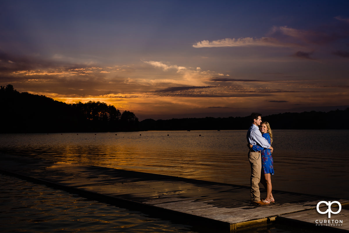 Engaged couple hugging on a dock by the lake on the Clemson University campus at sunset.
