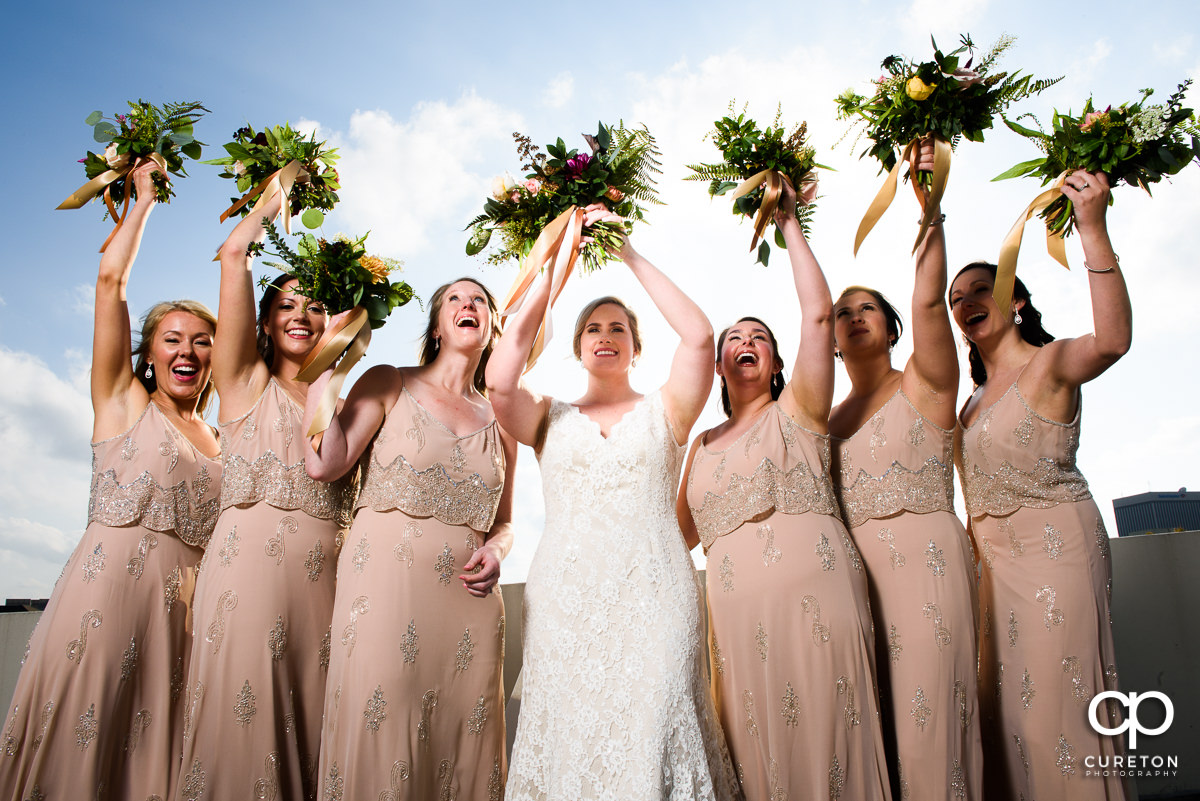 Bridesmaids throwing their flowers on a rooftop in Greenville.