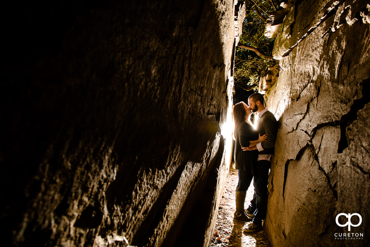Bride and groom kissing inside of Devils Kitchen during their engagement session at Caesar's Head State Park.