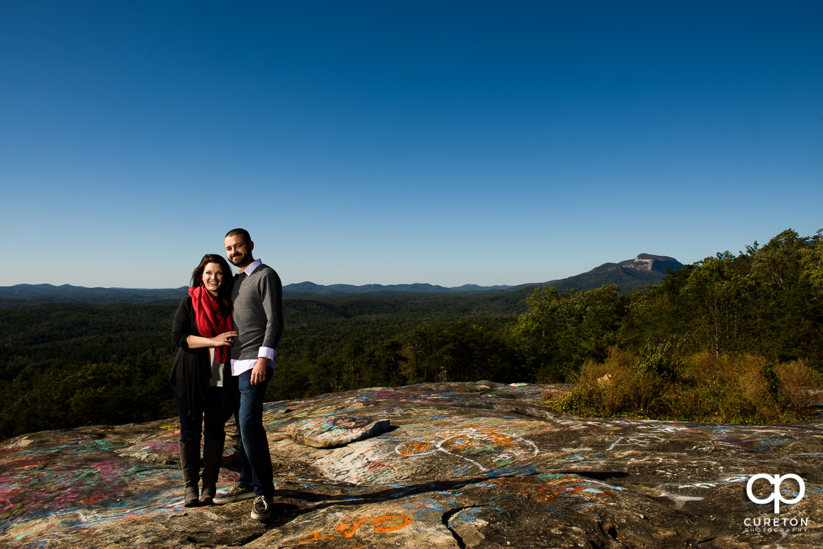 Man and his fiancee standing on Bald Rock during their engagement session.