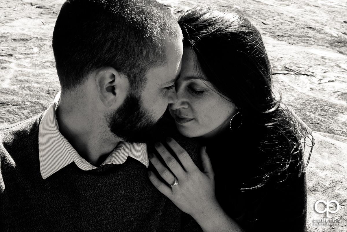 Engaged couple cuddling tight.