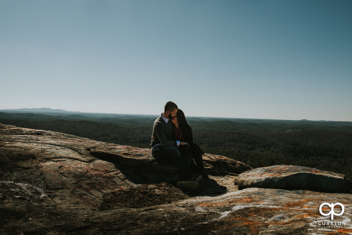 Man and woman sitting on Bald Rock at the end of their engagement session.