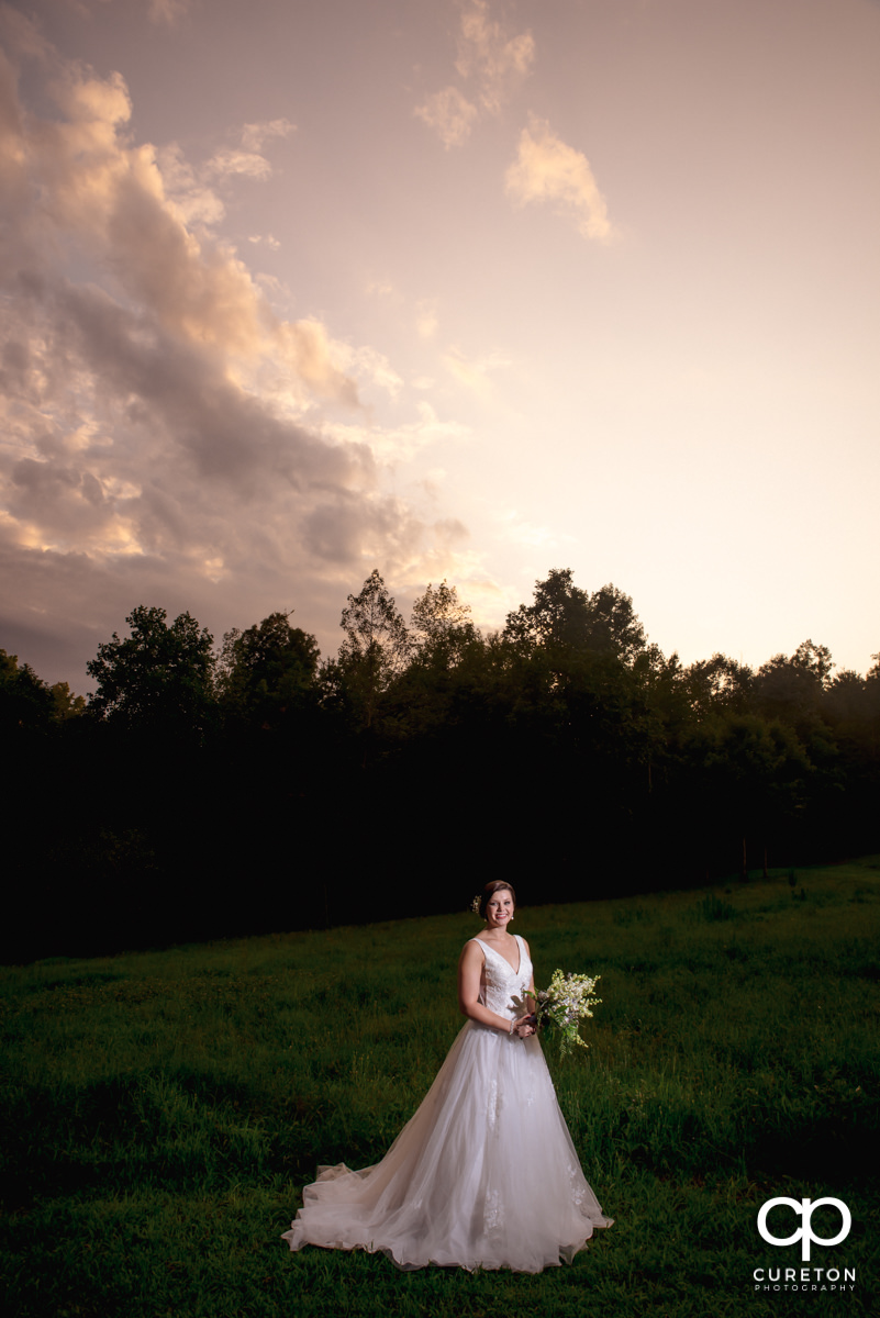 Bride in a field at sunset at a bridal session at Campbell's Covered Bridge in Greer,SC.