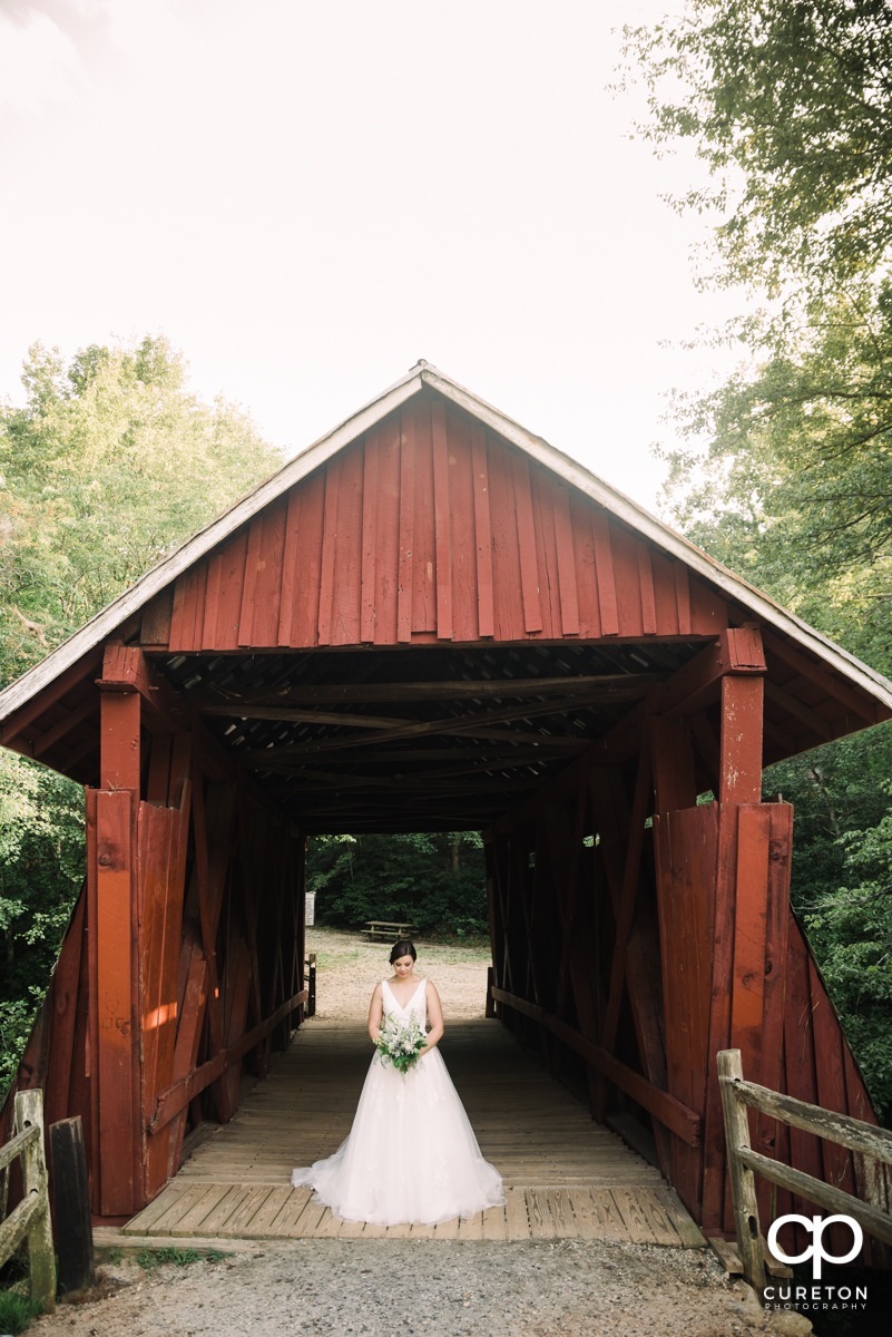 Bride in front of a covered wooden bridge.