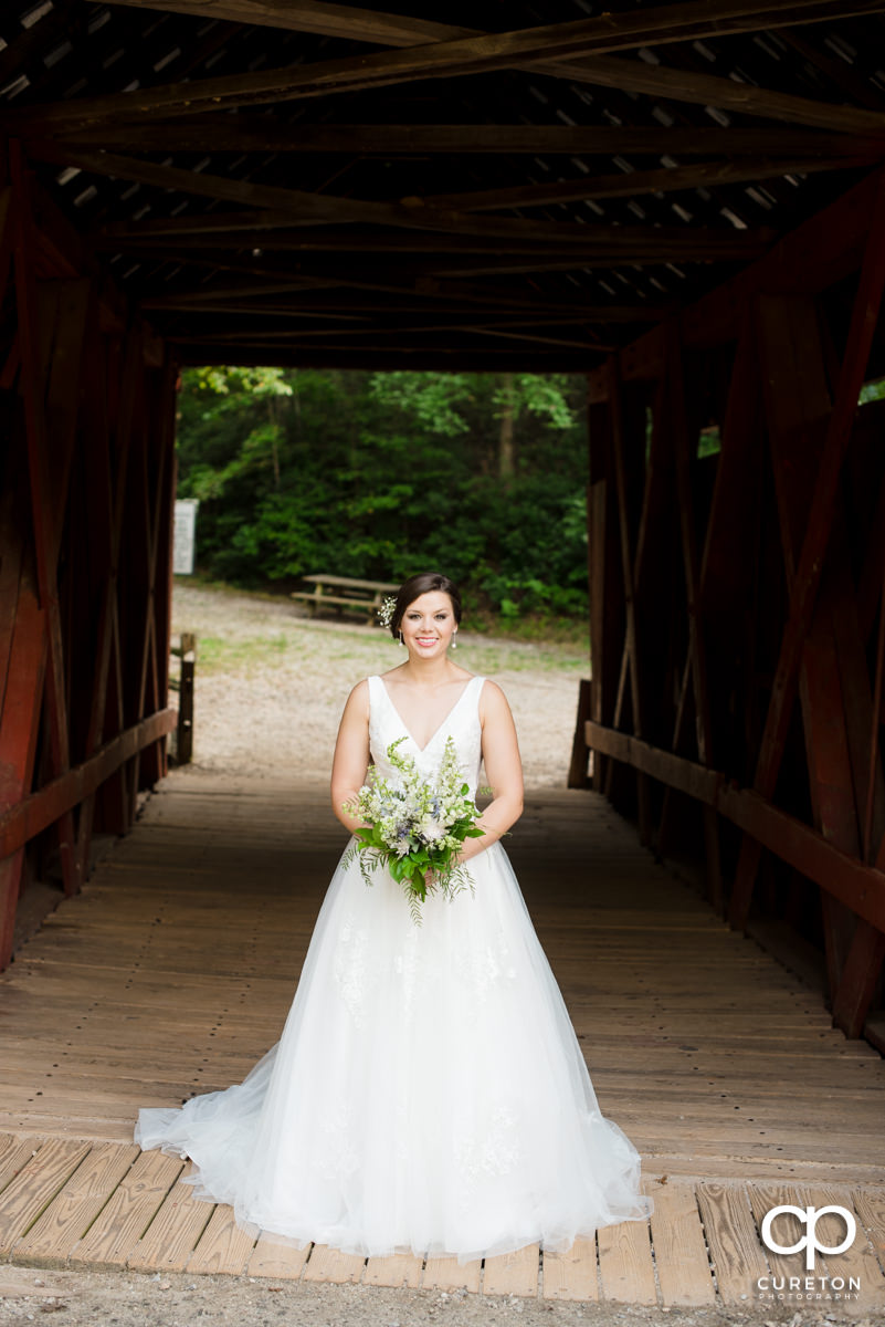 Bride standing in a covered wooden bridge.