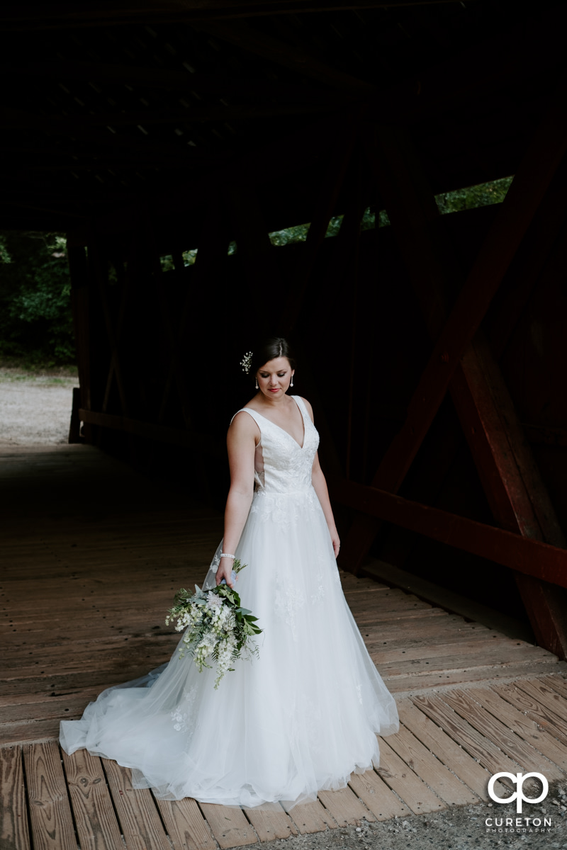 Bride looking at her flowers in an antique wooden covered bridge.