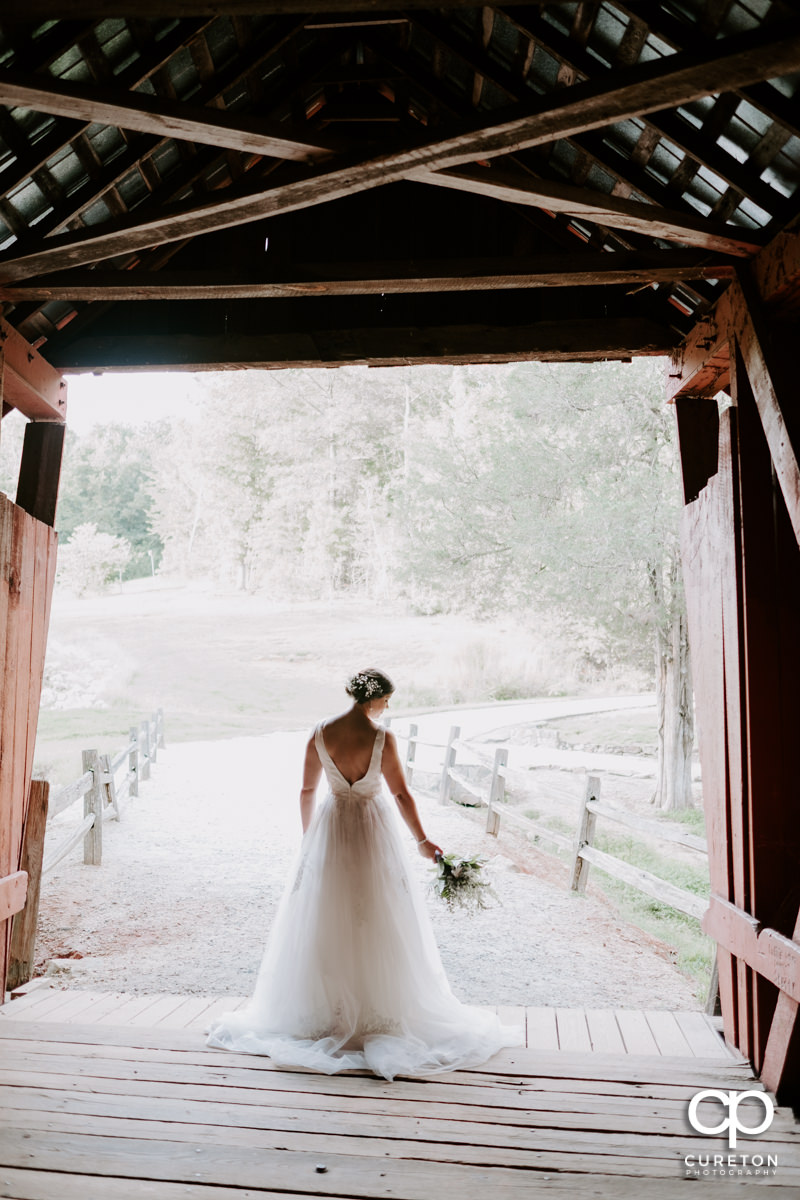 Bride holding her flowers as she walks out of an antique covered bridge.
