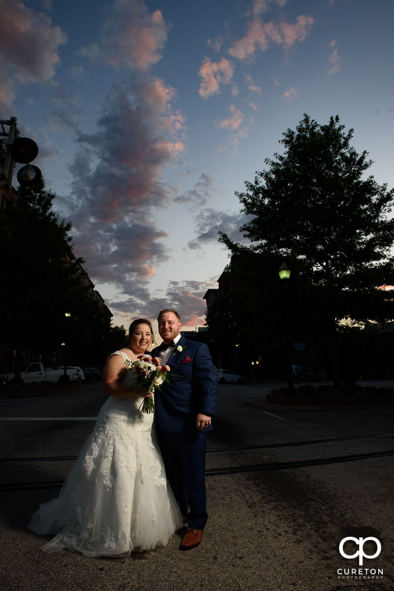 Bride and groom standing in Main St. at sunset after their wedding at the Old Cigar Warehouse in downtown Greenville,SC.