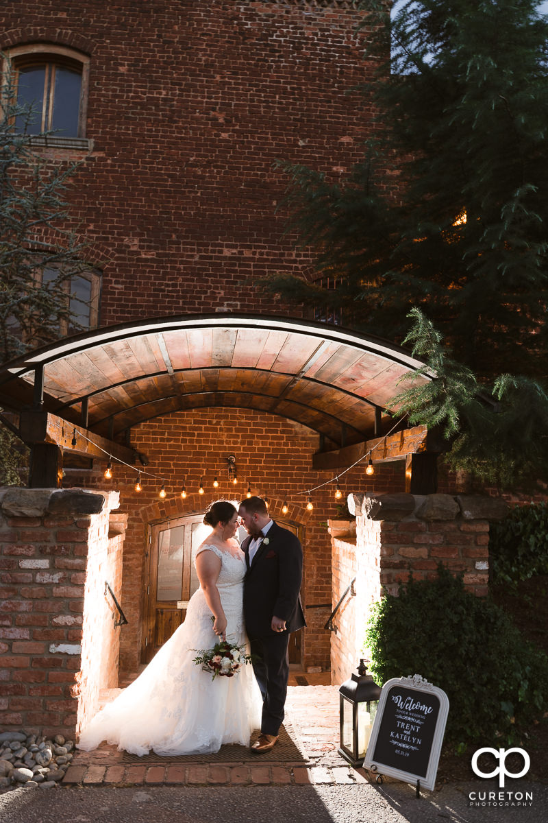 Groom and bride leaning into each other in front of twinkling lights at the side entrance of their wedding at the Old Cigar Warehouse in Greenville,SC.