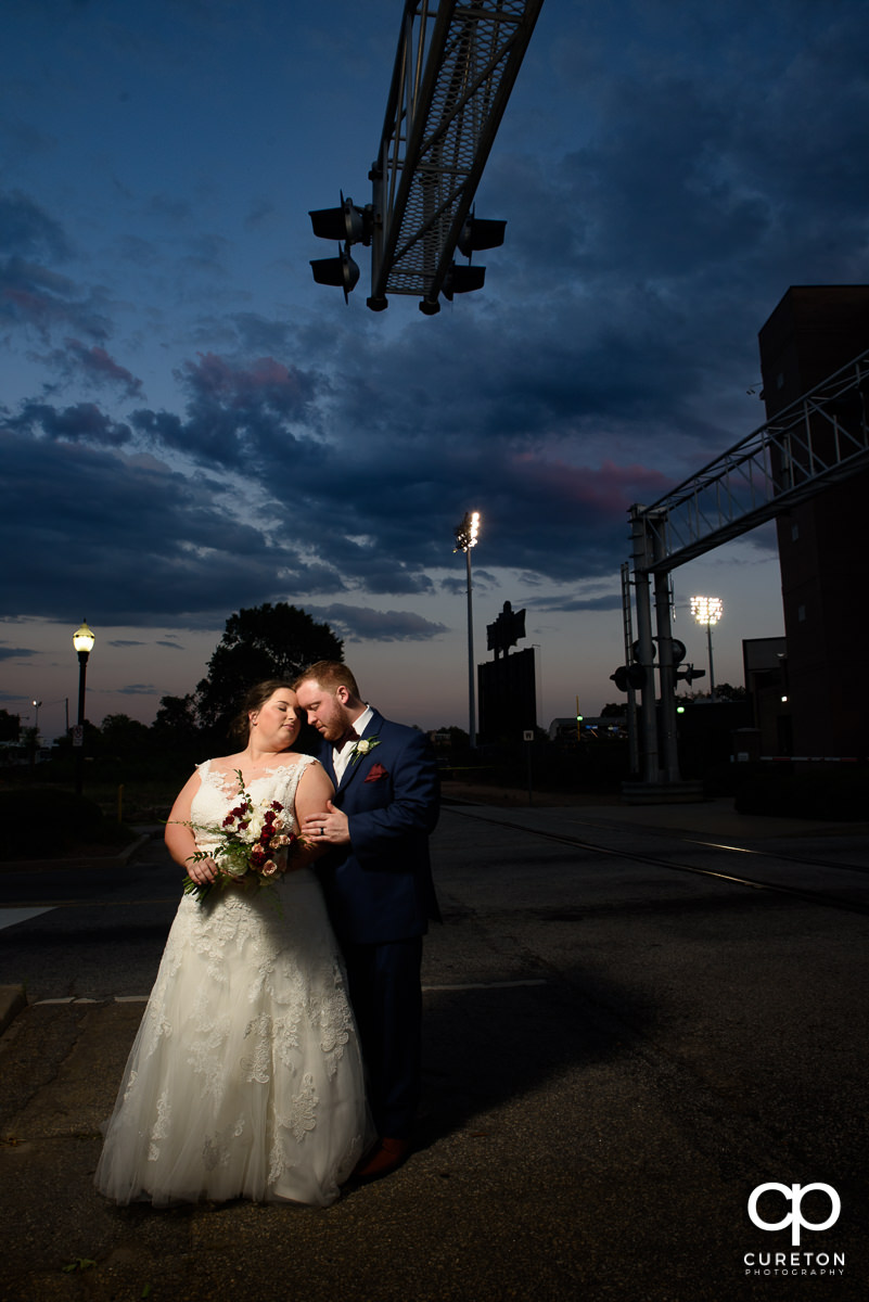 Groom snuggling with his bride at sunset after their wedding at the Old Cigar Warehouse in Greenville,SC.