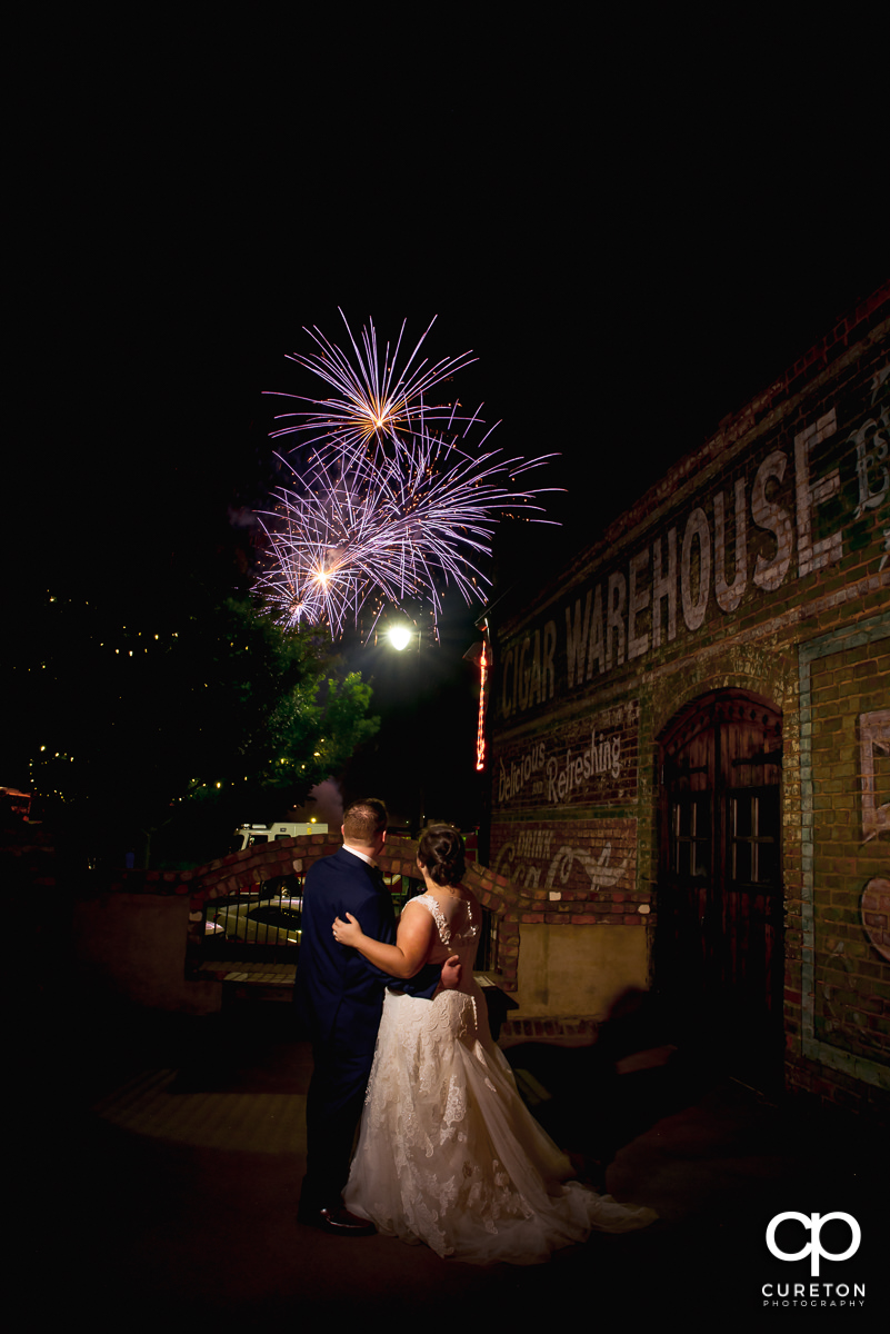 Bride and groom watching the fireworks show from the deck of The Old Cigar Warehouse after their wedding in downtown Greenville .
