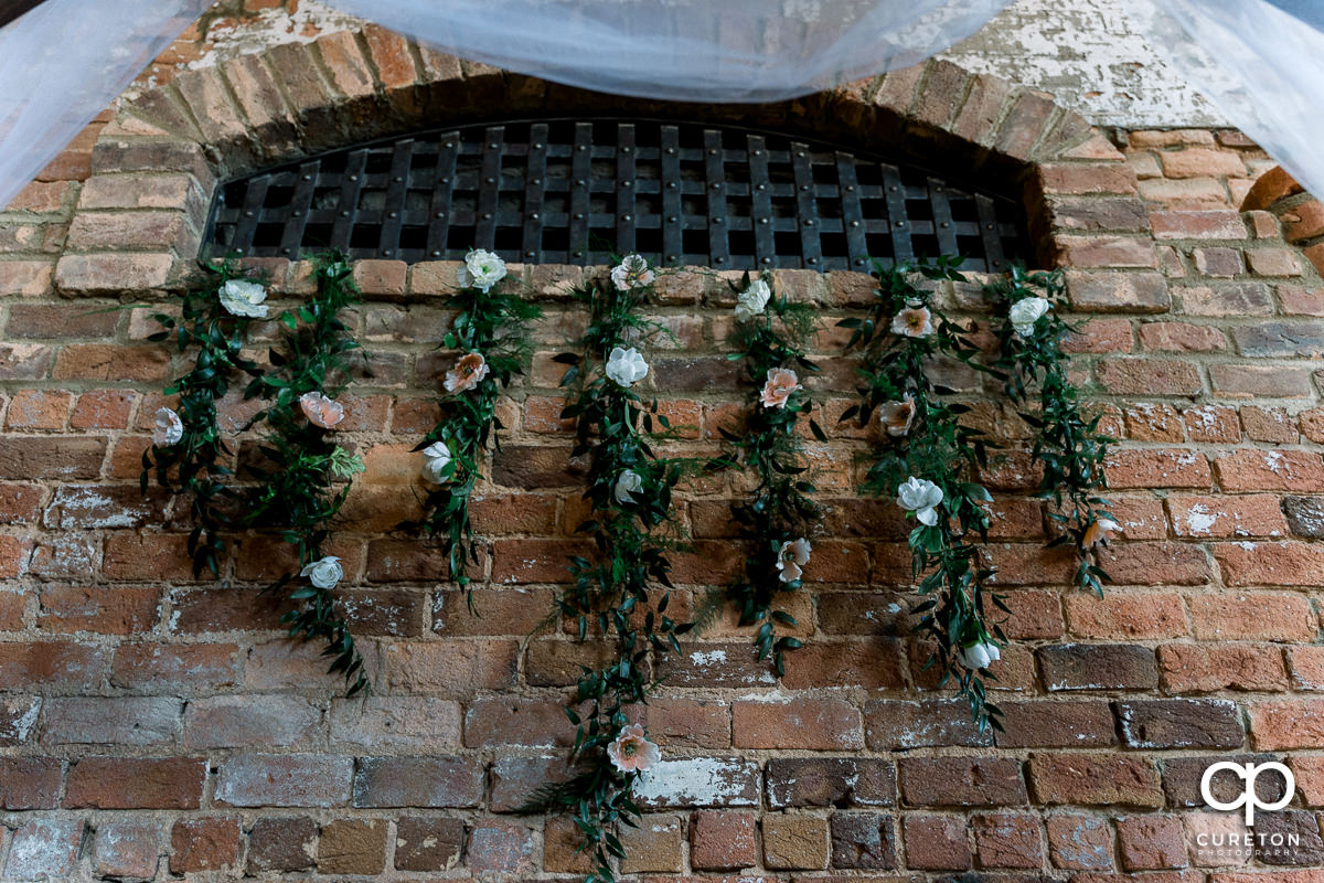 Flowers hanging out of a vent underneath the alter.