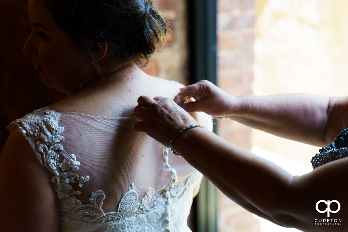 Bride being put into her dress.