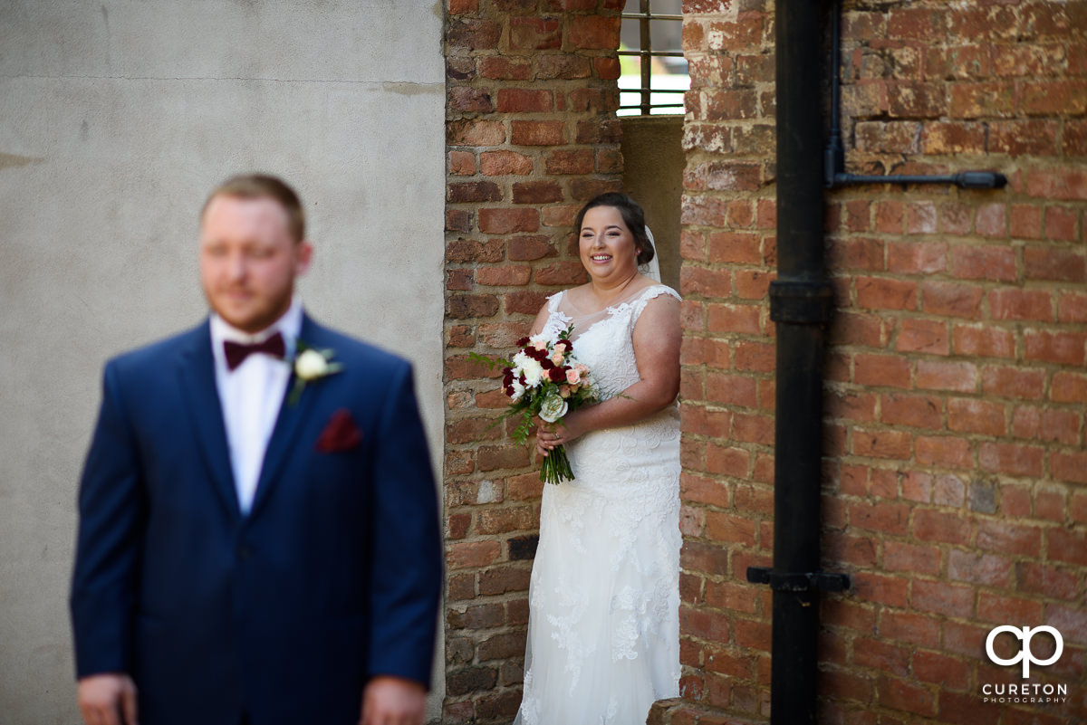 Bride walking up on the groom at the first look before the Old Cigar Warehouse wedding ceremony.