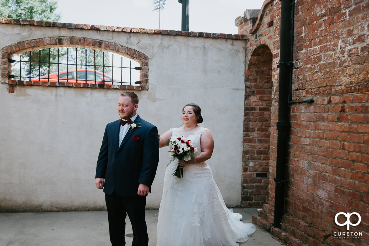 Bride tapping the groom on the shoulder at the first look before the Old Cigar Warehouse wedding ceremony.