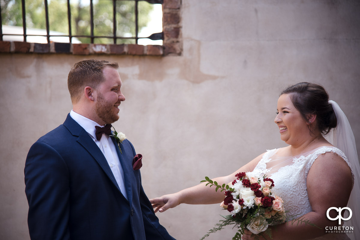 Bride and groom smiling at each other at the first look before the Old Cigar Warehouse wedding ceremony.