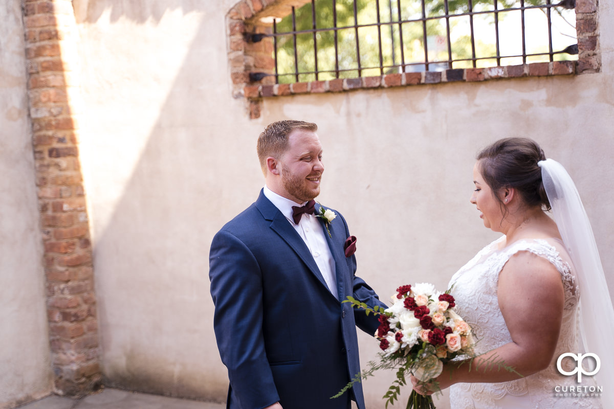 Groom smiling at his bride at the first look before the Old Cigar Warehouse wedding ceremony.