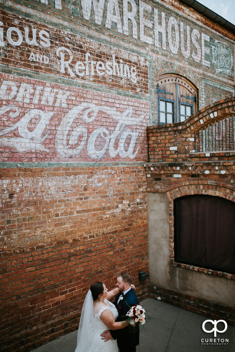 Bride and groom dancing in front of the Coca-Cola mural at The Old Cigar Warehouse in downtown Greenville before the wedding ceremony.