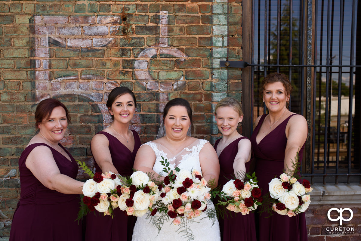 Bride and her bridesmaids showing their flowers.
