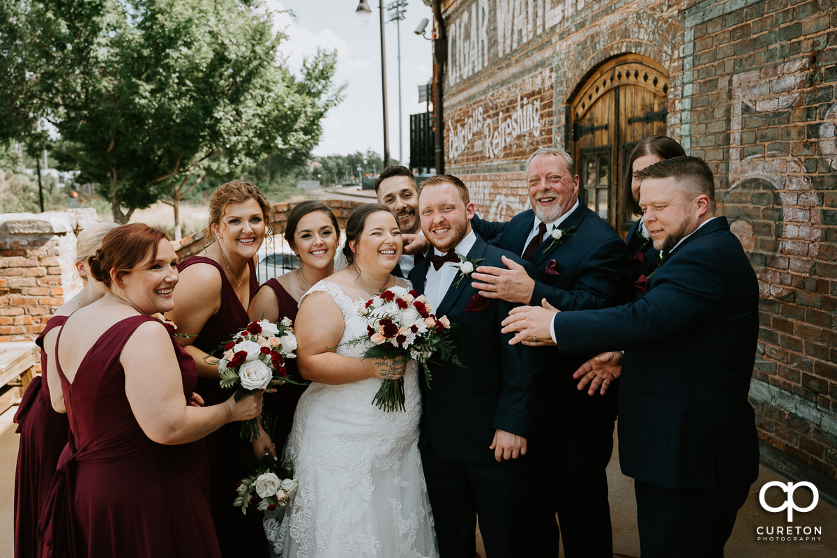 Bridal party hugging the bride and groom.