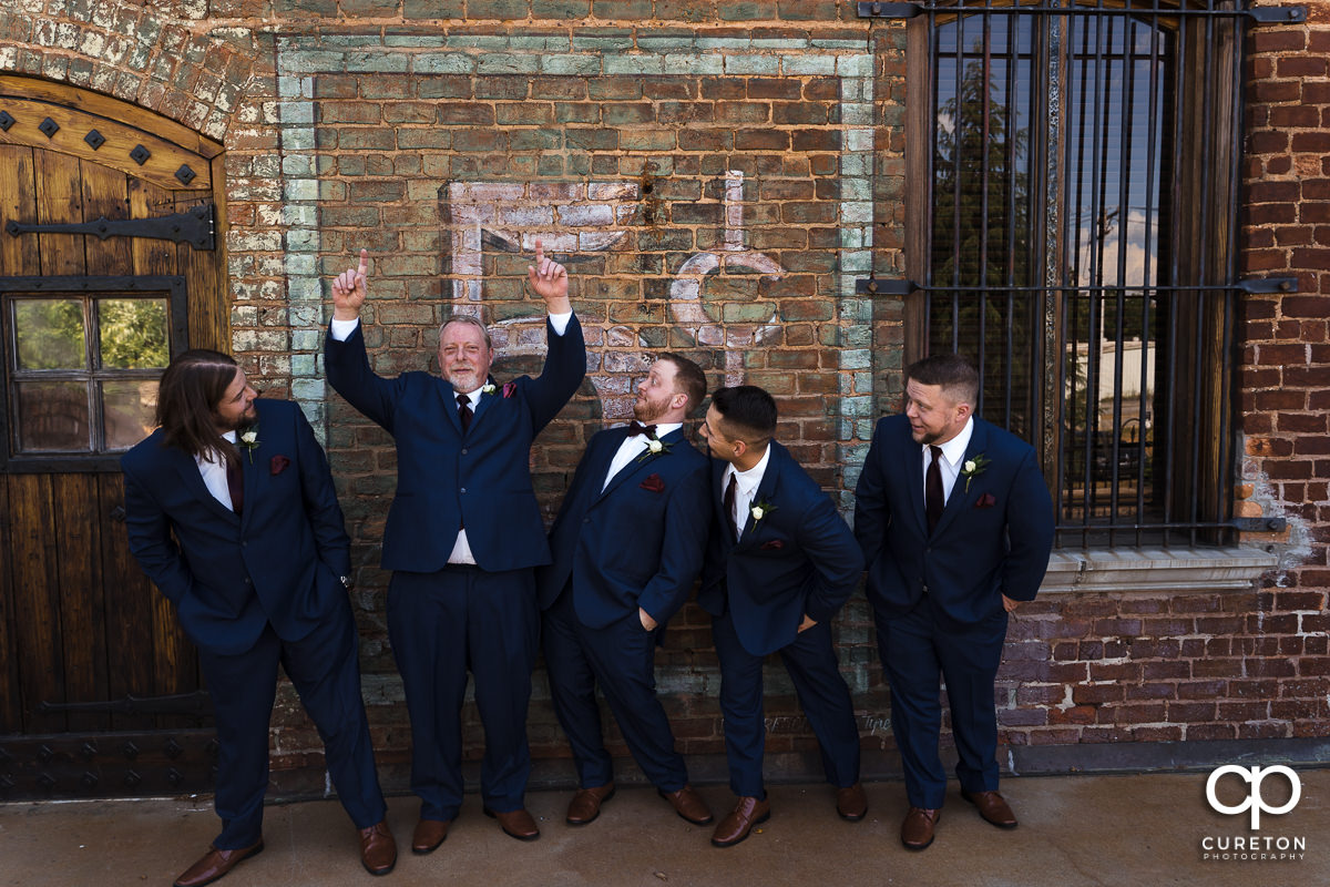 Groomsmen cutting up at The Old Cigar Warehouse in downtown Greenville before the wedding ceremony.