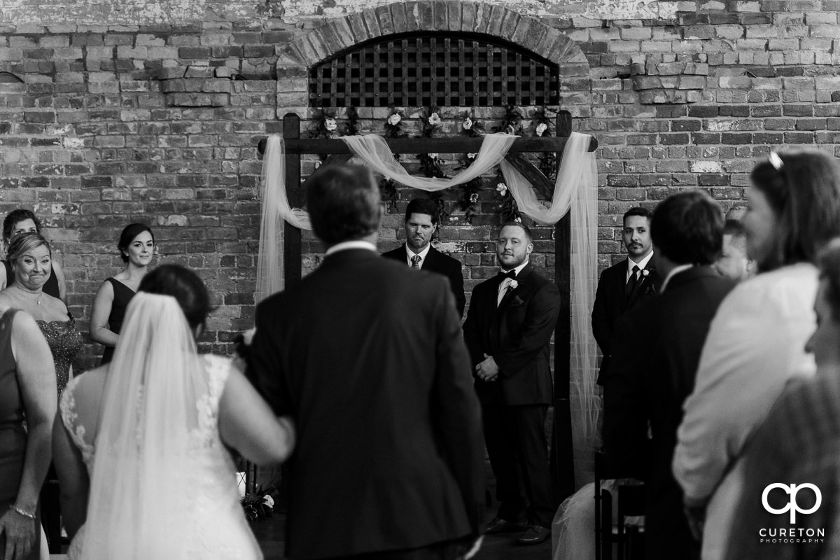 Groom seeing his bride walking down the aisle at the wedding ceremony.