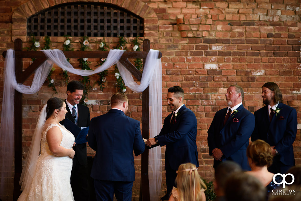 Best man giving the groom the rings.