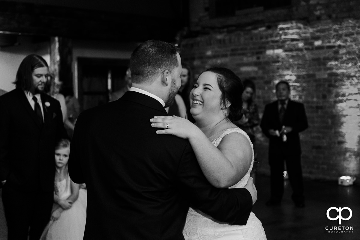 Bride laughing during the first dance at the wedding reception in Greenville at The Old Cigar Warehouse.