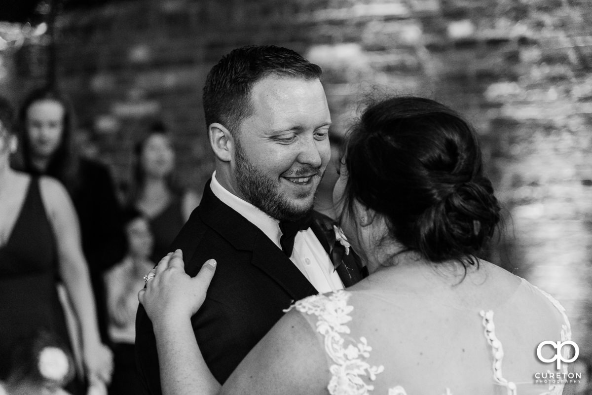 Groom smiling at his bride during their first dance at the wedding reception in Greenville at The Old Cigar Warehouse.