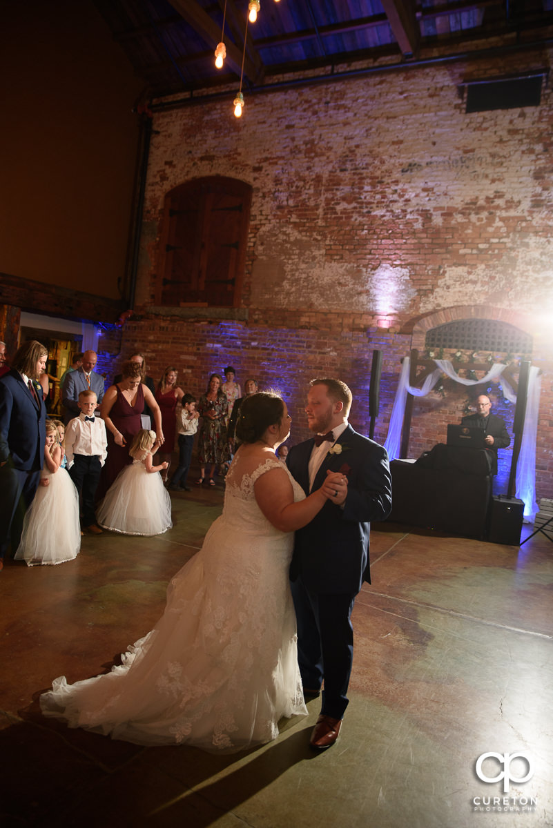 Bride and groom sharing a dance at the wedding reception in Greenville at The Old Cigar Warehouse.