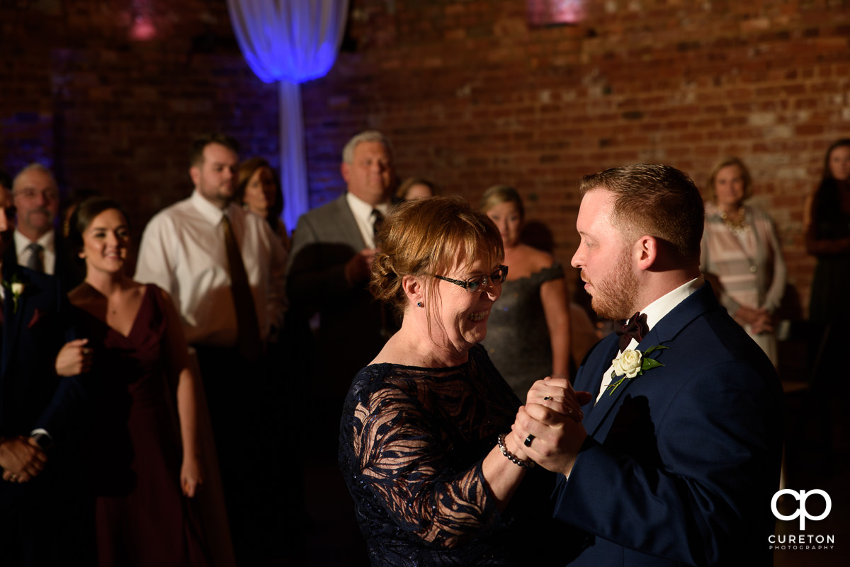 Groom dancing with his mom at the wedding reception in Greenville at The Old Cigar Warehouse.