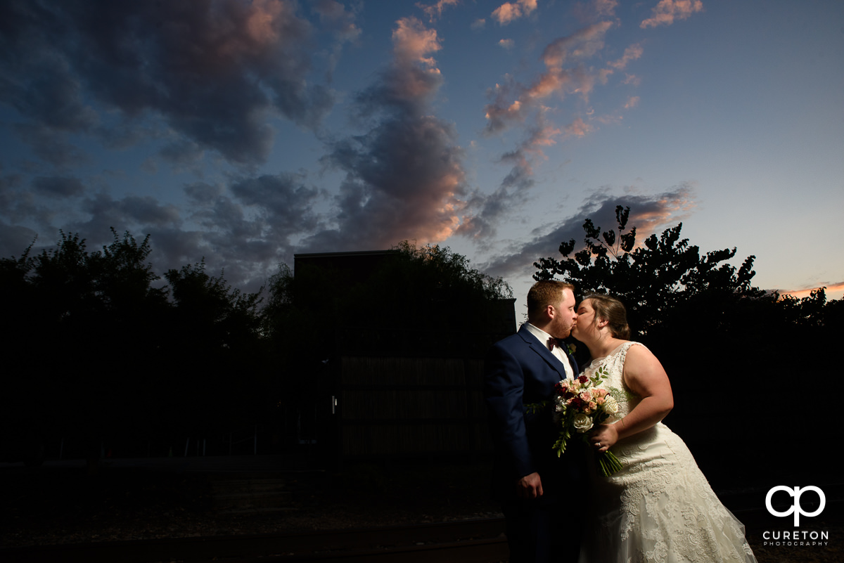 Bride and groom kissing at sunset at the wedding reception in Greenville at The Old Cigar Warehouse.