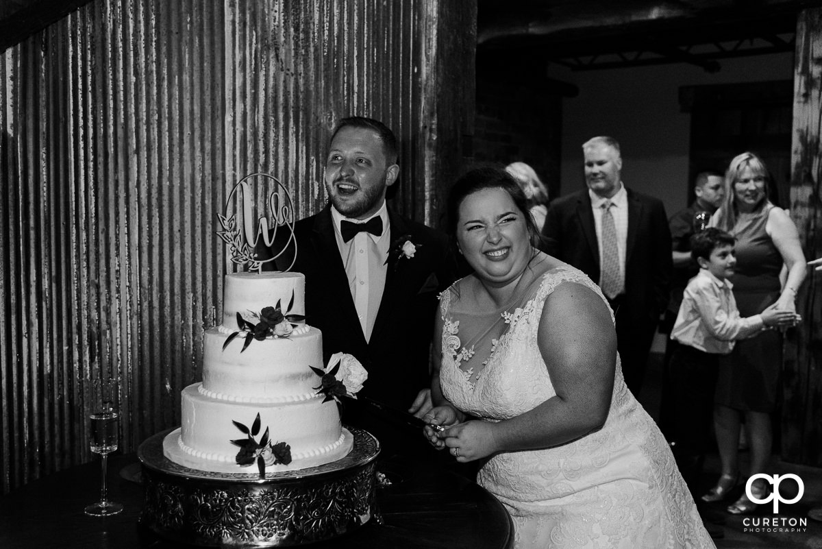 Bride and groom laughing while cutting the cake.