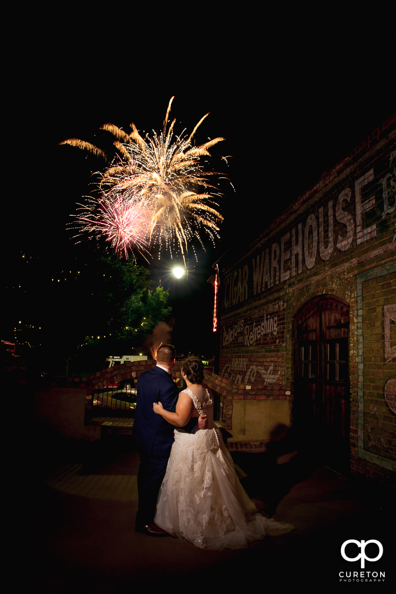 Bride and groom watching the fireworks show in downtown Greenville from the deck of The Old Cigar Warehouse at their wedding reception.