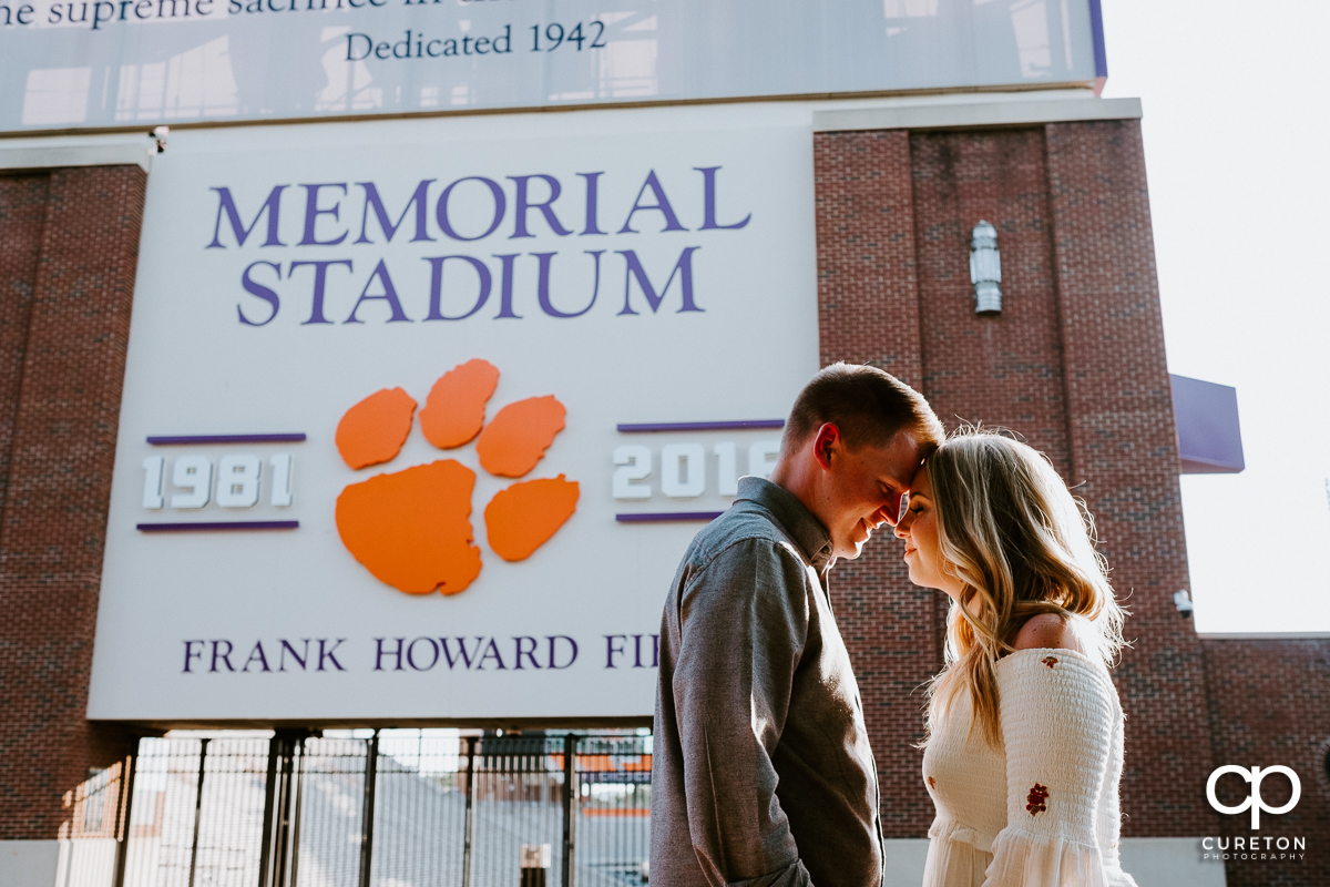 Future bride and groom standing outside Memorial Stadium (Death Valley) during their engagement session in Clemson,SC.