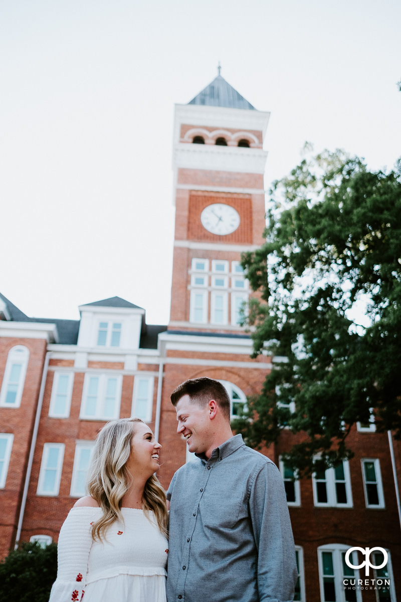 Engaged couple staring into each other's eyes in front of Tillman Hall during a Clemson engagement session.