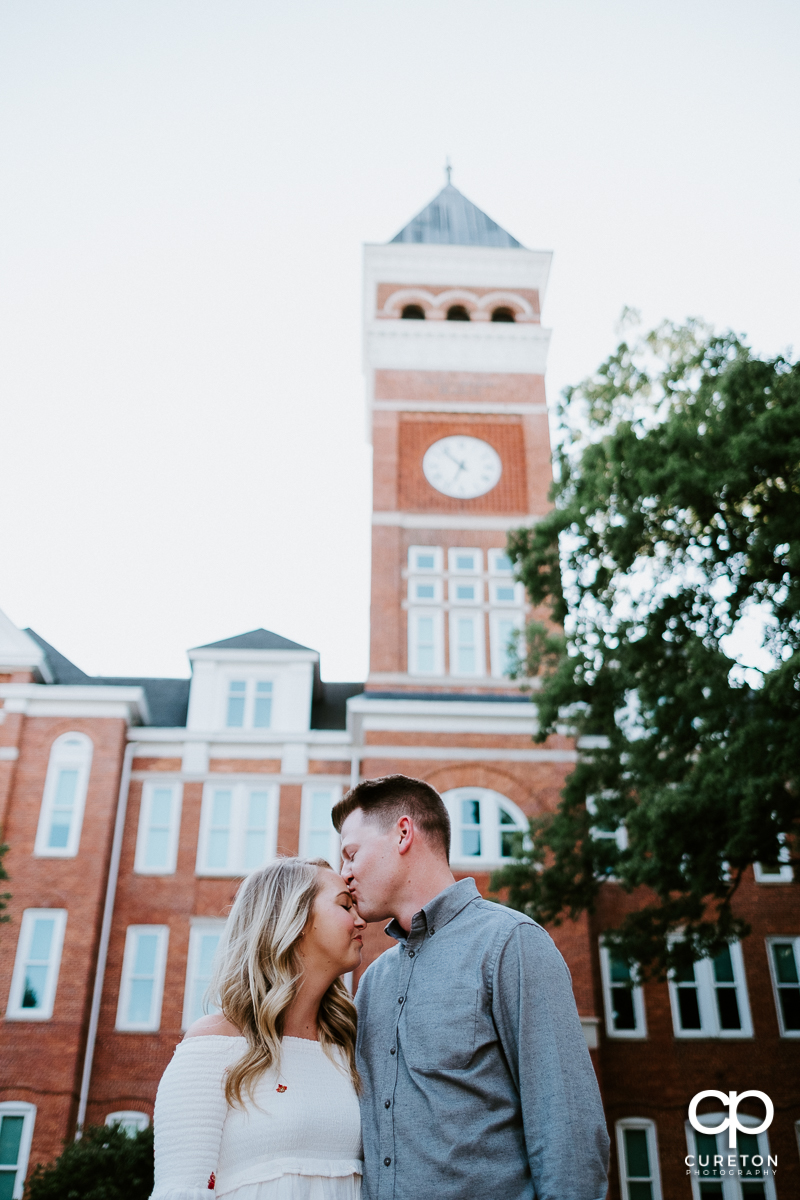 Man kissing his fiancee on the forehead in front of Tillman Hall.