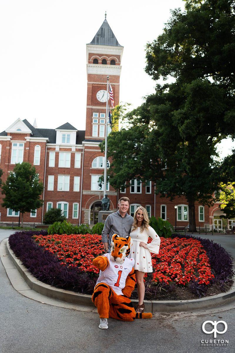 Future bride and groom outside Tillman Hall during their engagement session with the Clemson Tiger mascot.