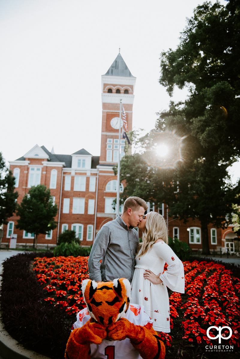 Engaged couple kissing in front of Tillman Hall while the Clemson Tiger Mascot covers his eyes.