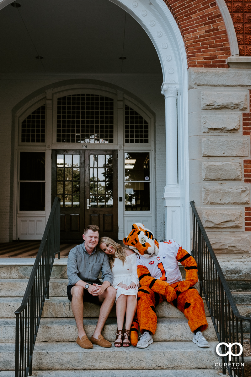 Engaged couple leaning on each other and the Clemson Tiger during an engagement session with the mascot.