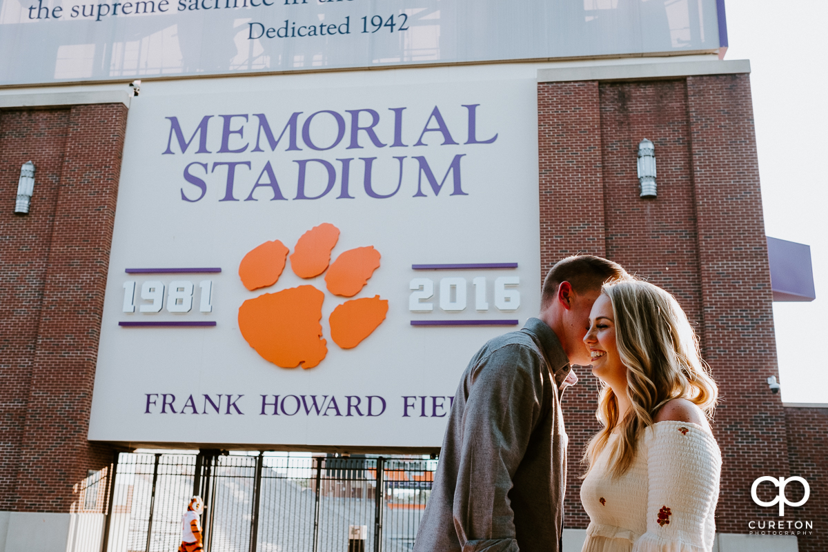 Man making his future bride laugh in front of a football stadium.