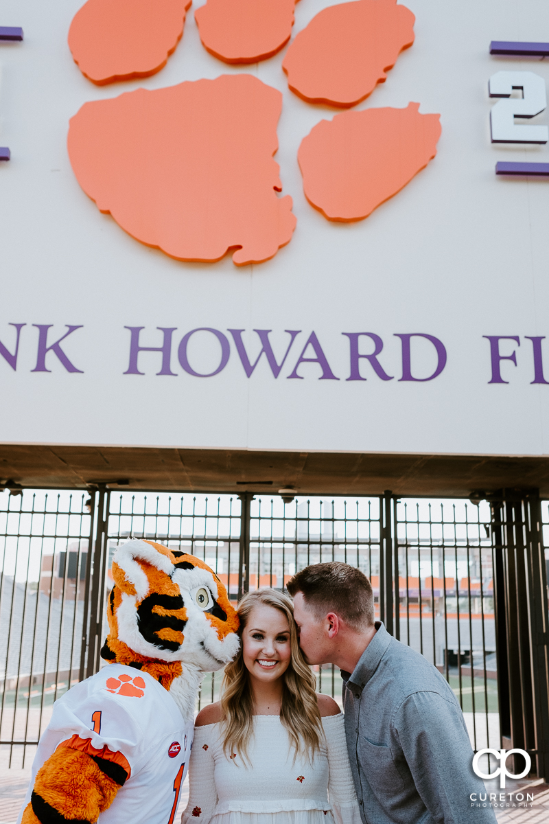 Woman being kissed on the cheek by both her fiancee and the Tiger mascot during an engagement session in Clemson,SC.