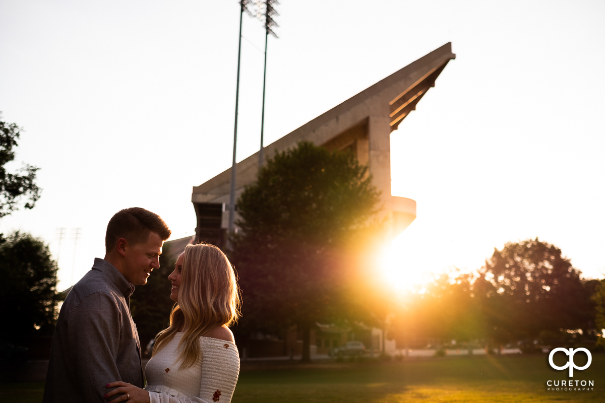 Engaged couple cuddling outside the stadium in Clemson.